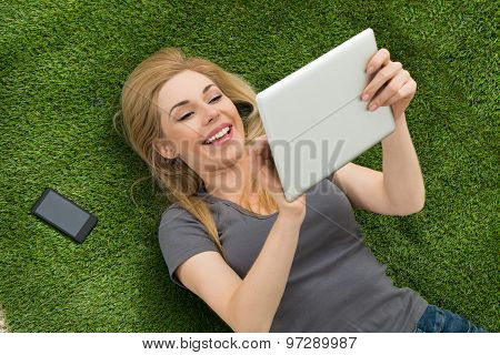 Woman Lying On Grass Using Digital Tablet