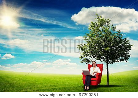 smiley businesswoman with laptop sitting on the red chair over beautiful landscape with green meadow, tree and blue sky