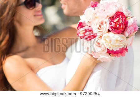 love, wedding, summer, dating and people concept - close up of couple with bunch of flowers hugging in city