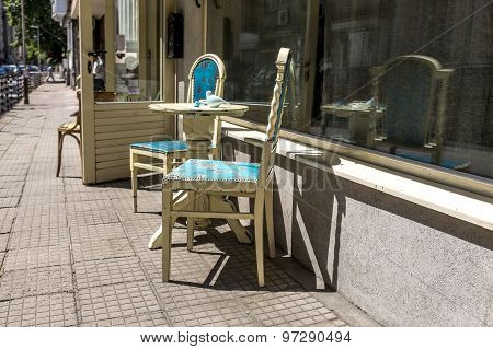 City Sidewalk With Cafe Table And Chairs