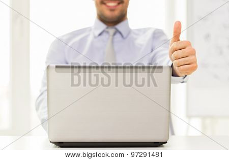 business, people, technology, gesture and teamwork concept - close up of businessman hands with laptop computer showing thumbs up at office