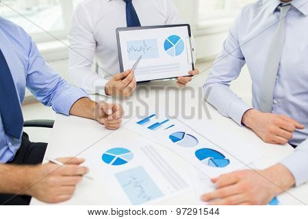 business, people, statistics and teamwork concept - close up of businessman hands with clipboard pointing pen to chart at office