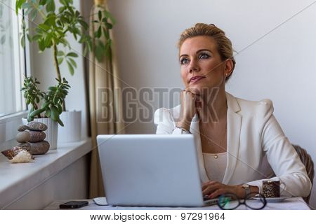 Young business woman sitting with laptop thoughtfully dreamy looks in the space.