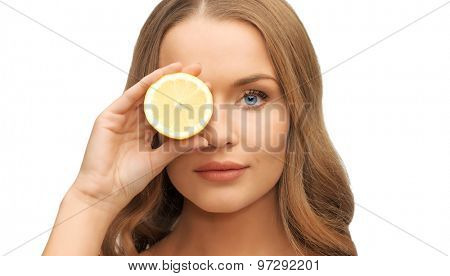 people and beauty concept - beautiful woman face with lemon slice over eye