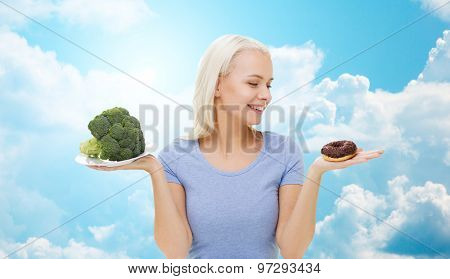 healthy eating, junk food, diet and choice people concept - smiling woman choosing between broccoli and donut over blue sky and clouds background