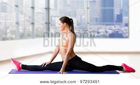 fitness, sport, exercising, stretching and people concept - smiling woman doing splits on mat over gym background