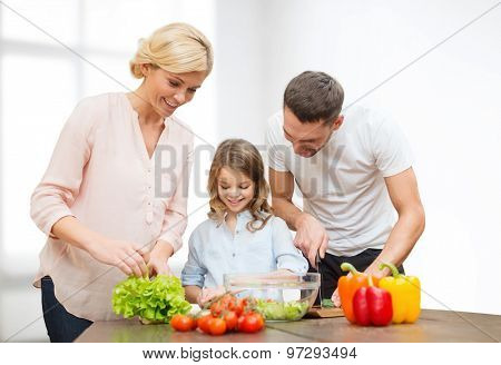 vegetarian food, culinary, happiness and people concept - happy family cooking vegetable salad for dinner over white room background