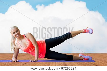 fitness, sport, exercising and people concept - smiling woman raising leg on mat over wooden floor and sky with white cloud background