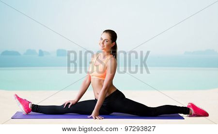 fitness, sport, exercising, stretching and people concept - smiling woman doing splits on mat over sea and pool at hotel resort background