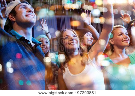 party, holidays, music events, nightlife and people concept - group of happy friends at hip-hop concert in night club