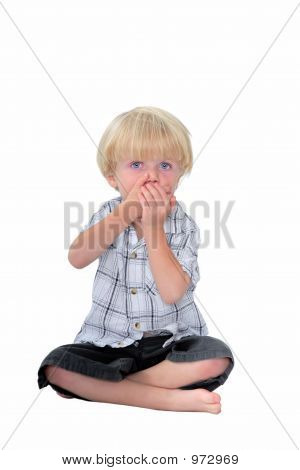 Young Boy With His Hands Over His Mouth And White Background