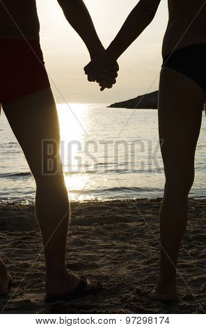 Couple On A Beach Holding Hands At Sunset