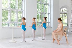 stock photo of ballet barre  - Three little ballerinas with personal classic ballet teacher in dance studio posing at ballet barre on a white - JPG