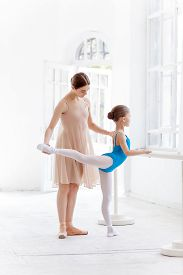 pic of ballet barre  - The little ballerina in tutu with personal classic ballet teacher in dance studio posing at ballet barre on a white studio background - JPG