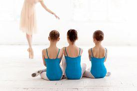 image of teachers  - Three little ballerinas with personal ballet teacher in dance studio - JPG