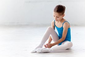pic of ballerina  - Beautiful little ballerina in blue dress for dancing sitting on the floor and puting on foot pointe shoes on white ballet studio background - JPG