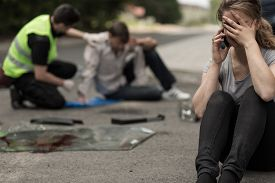 stock photo of accident victim  - Despair young female driver after traffic accident - JPG