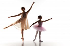stock photo of ballerina  - The silhouettes of little ballerina and personal classic ballet teacher in dance studio dancing on a white background - JPG