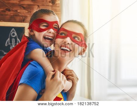 Mother and her child playing together. Girl and mom in Superhero costume. Mum and kid having fun, sm