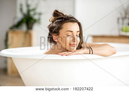 poster of Beautiful young woman relaxing lying in the bathtube in the bathroom