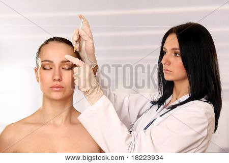 beautician giving an injection on the female face