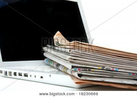 pilha de jornal ao lado de um laptop