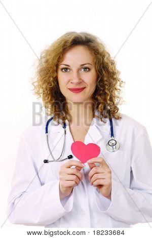 Uma médica sorrindo, examinando um coração vermelho em forma de travesseiro com um estetoscópio contra backgro branco