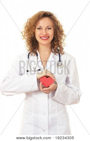A smiling female doctor examining a red heart shaped pillow with a stethoscope against white background