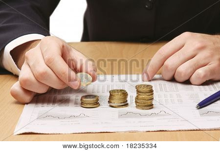 Businessman putting the coins in columns