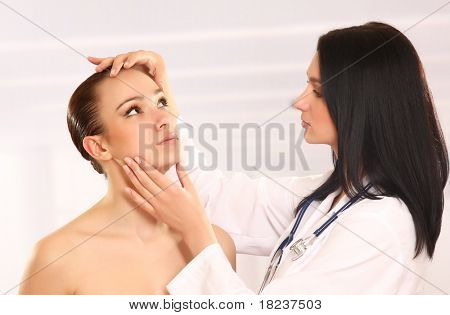 Bastante doctor examinando la cara de la mujer joven hermosa