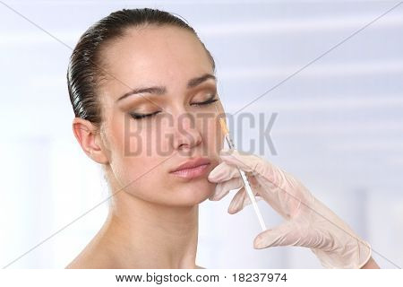 The Beautiful woman getting injection against aging process.