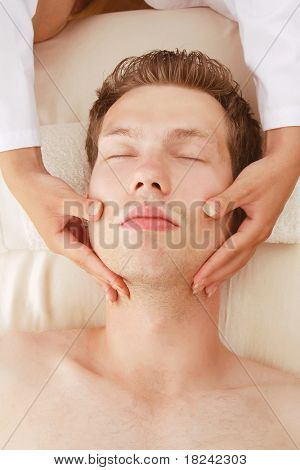 Closeup of a man receiving facial massage from a woman