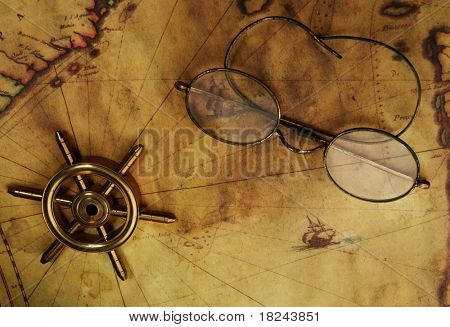 Glasses and sea wheel on the old map