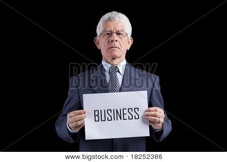 Senior businessman holding a paper with the Business word (isolated on black)