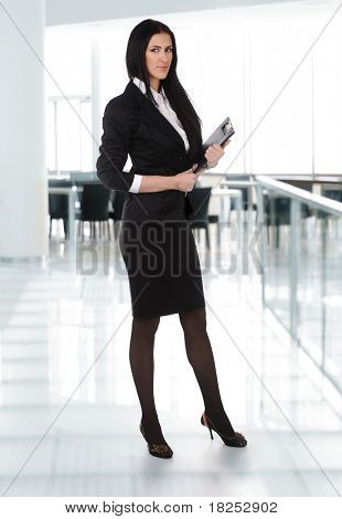 Full length young business woman standing with her clipboard on steps