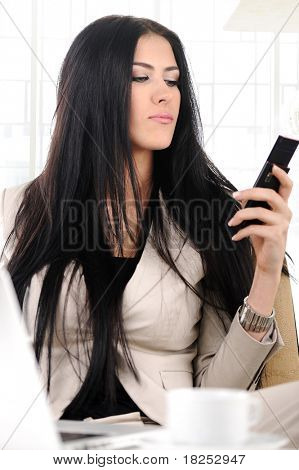 View of beautiful business woman holding cell phone and typing sms messages