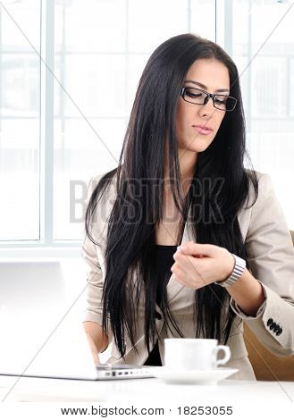 Office portrait of beautiful young business woman looking at her watch in office