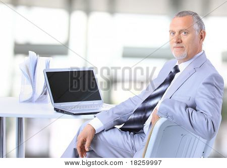 Portrait of a happy senior entrepreneur displaying computer laptop in office