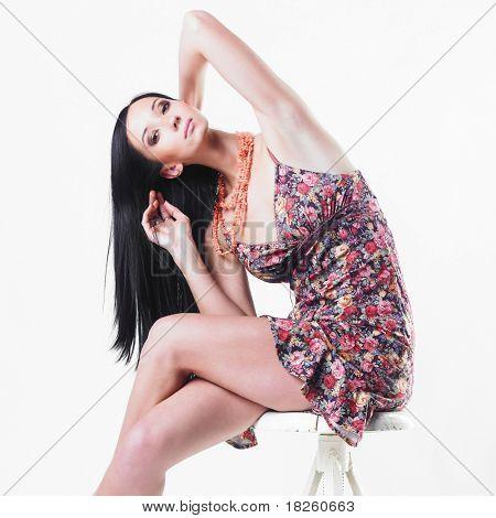 Schöne Frau, die auf weißen Stuhl sitzend