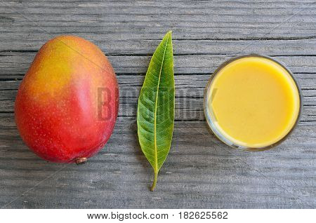 poster of Fresh mango smoothie,ripe mango fruit and mango tree leaf on old wooden table background.Healthy food,diet or vegan food concept.Top view.