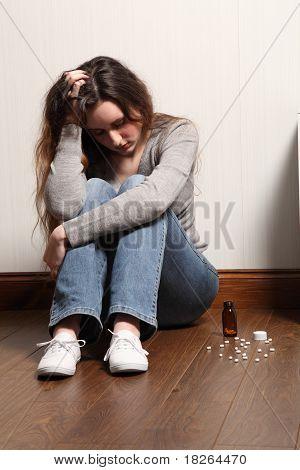 Teenage Girl Depressed Sitting With Pills On Floor