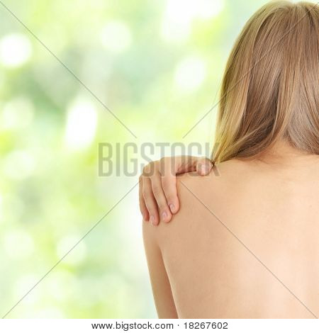 Woman from behind, naked body, pain concept,against abstract green background