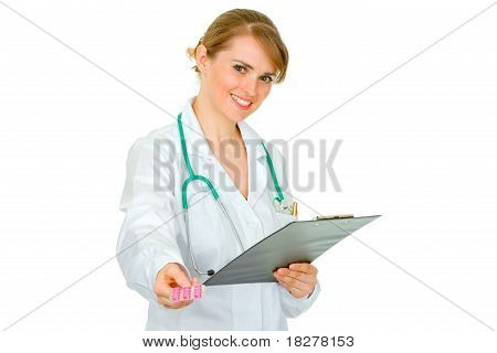 Smiling medical doctor woman holding clipboard and prescription drugs in hands isolated on white