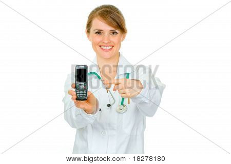 Smiling medical female doctor pointing finger on mobile with blank screen isolated on white