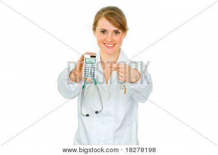 Smiling medical doctor woman pointing finger on calculator isolated on white