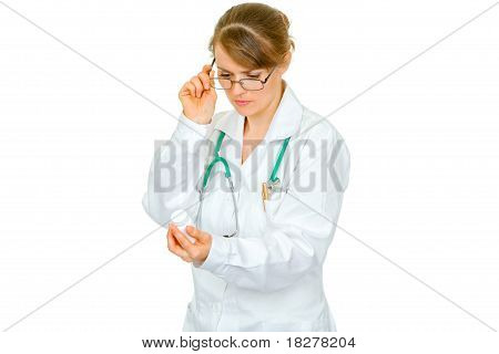 Concentrated medical female doctor in eyeglasses reading name of drug isolated on white