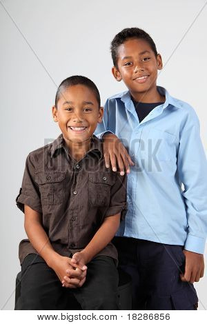 Two school boys pose happily together in studio