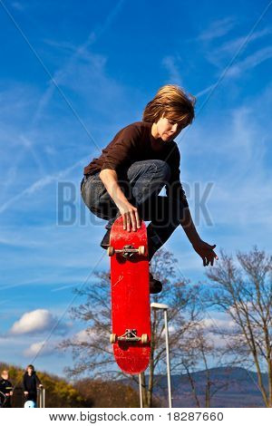 boy is jumping high with his skateboard