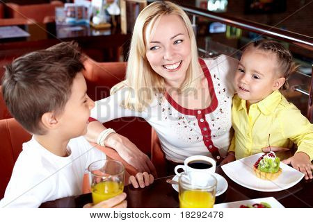 Portrait of happy woman with her two cute children in cafe