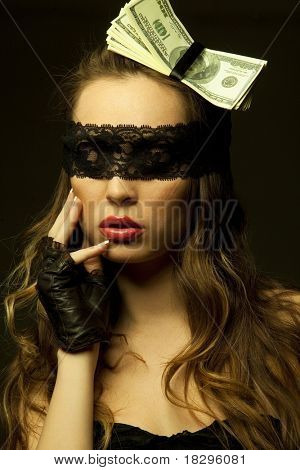 Beautiful sexy woman head-dressed with dollars  looking through black openwork lace in darkness